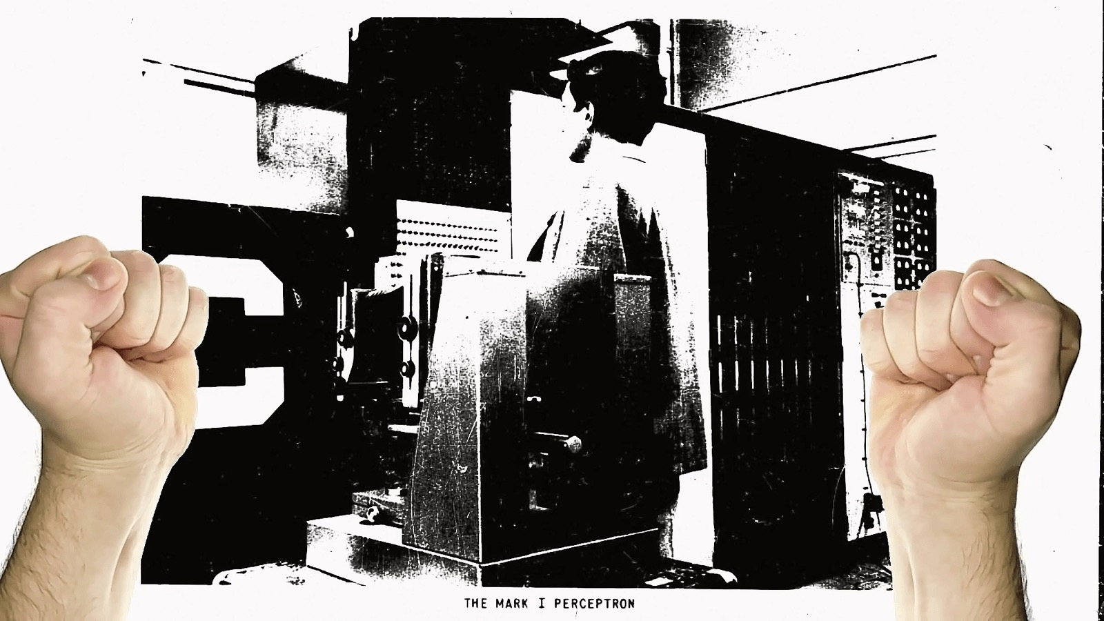 A picture of two hands above an old, grainy image of the Mark I Perceptron, a machine for pattern recognition.